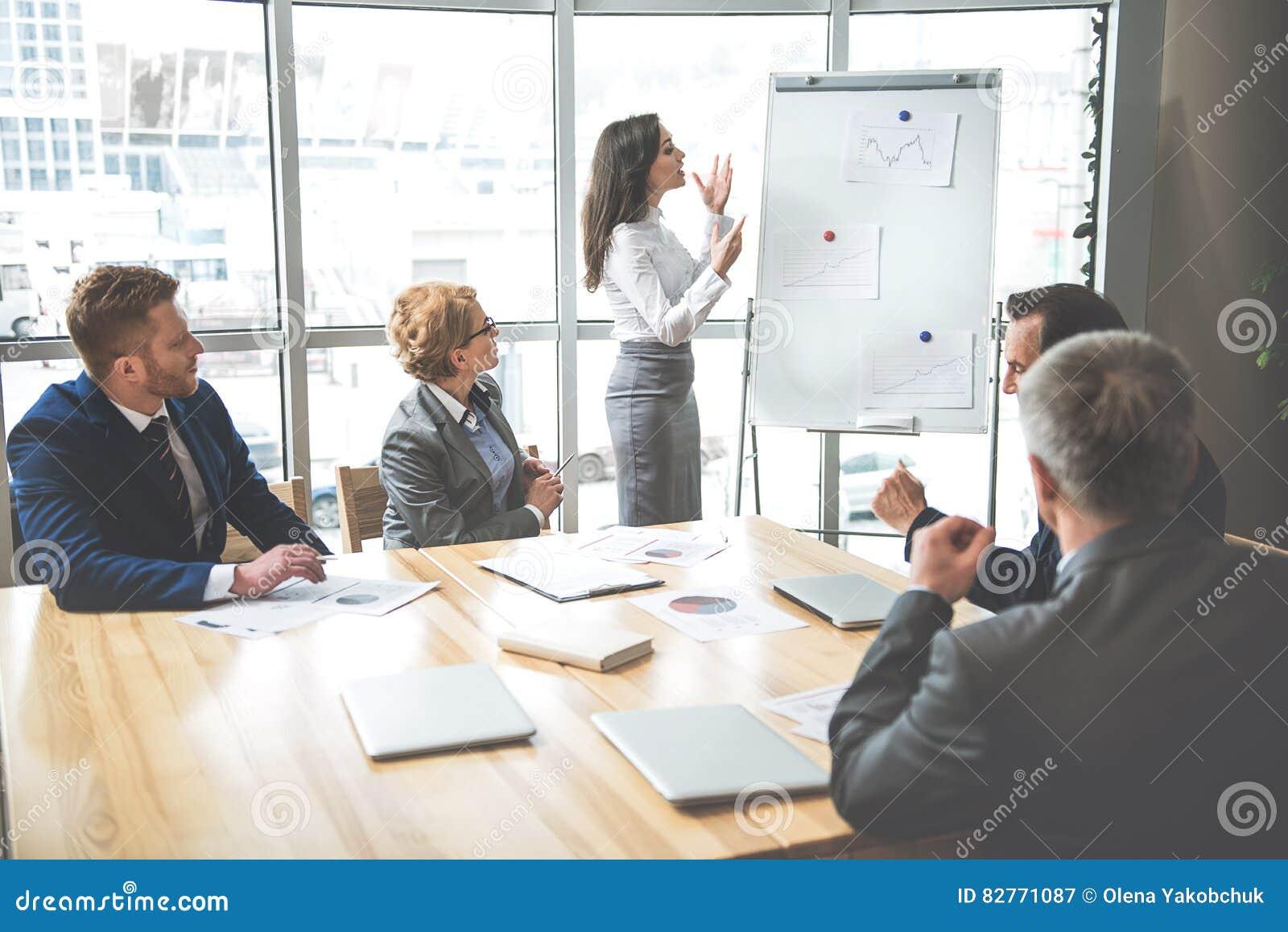 fda9e2fcc17be Las mujeres jovenes confiadas se están colocando cerca del tablero y de  hablar El grupo de trabajadores está escuchando ella