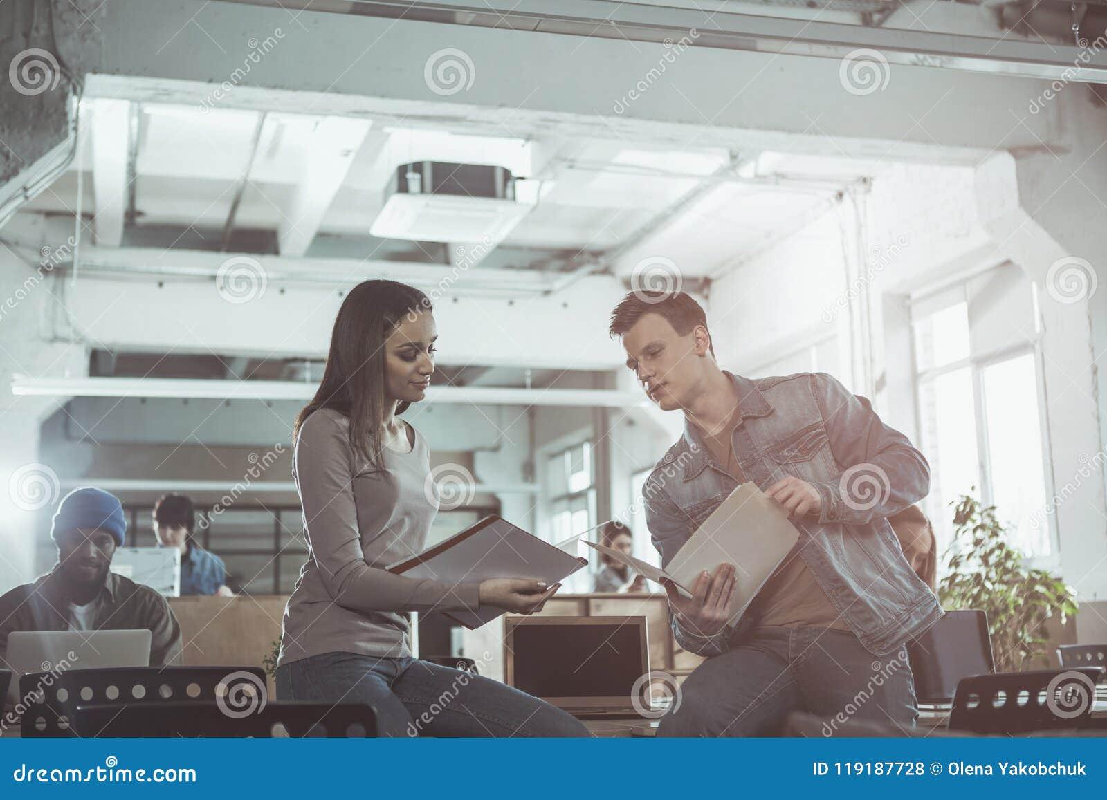 89f7b0140b921 Compruébelo El ángulo bajo del varón profesional concentrado y la hembra se  están sentando en la tabla en oficina La muchacha está mostrando sus  documentos ...