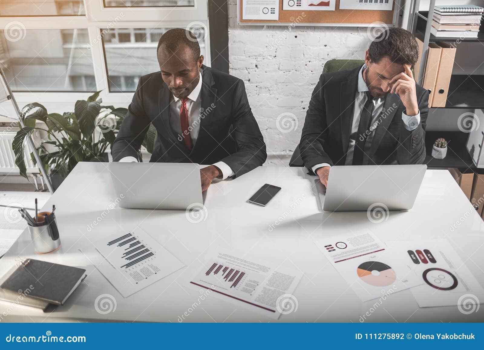 584e060aa6b0d Implicado en la lectura La opinión superior dos encargados concentrados se  está sentando en la tabla y está trabajando en los ordenadores portátiles  ...