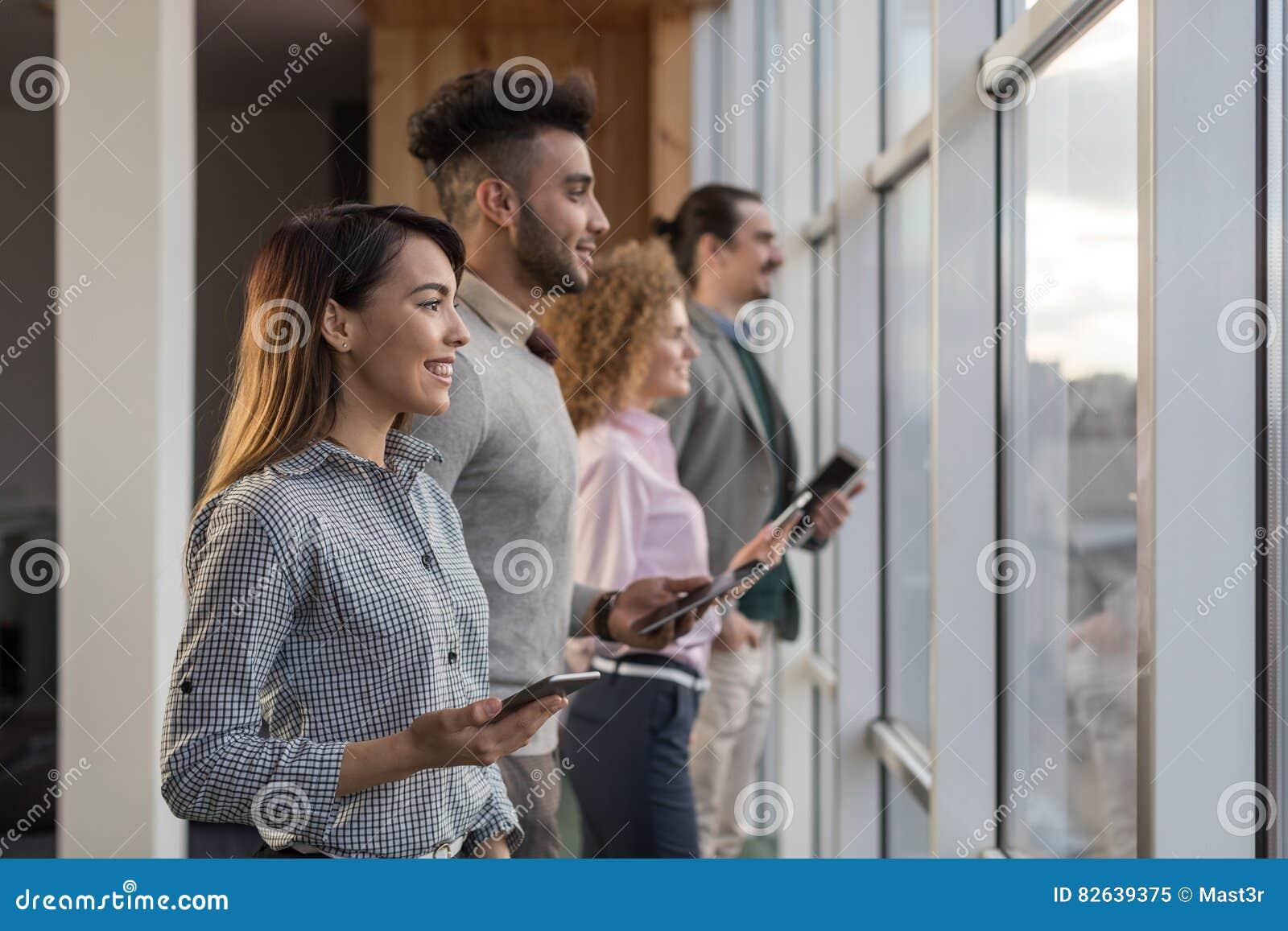 Los empresarios en Coworking centran el negocio Team Coworkers Using Tablet Computers que se sienta en ventana panorámica delante