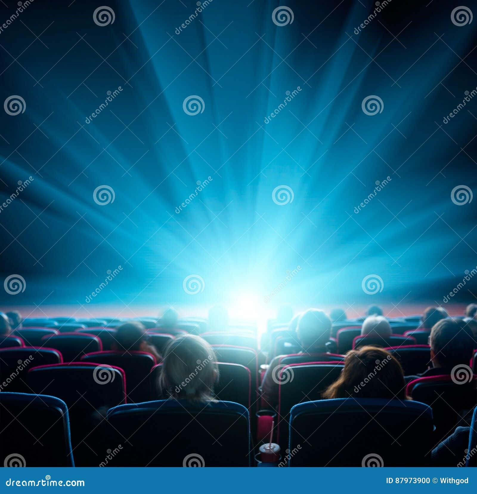 Los espectadores miran la luz brillante en el cine