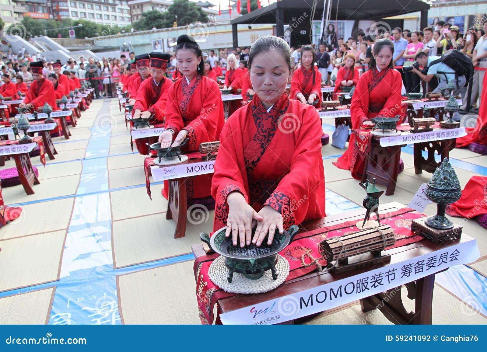 Los estudiantes chinos y extranjeros con una bendición del hanfu recolectaron en la torre de reloj en la ceremonia