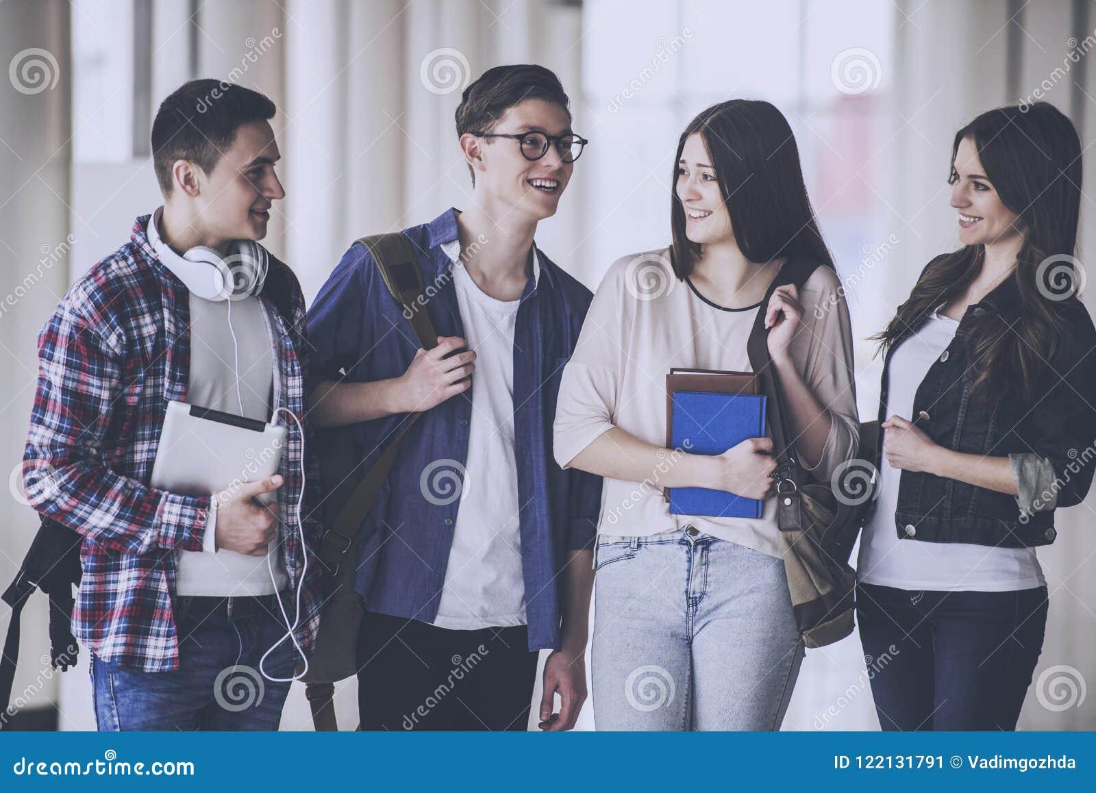 Los estudiantes jovenes felices están hablando en el Pasillo