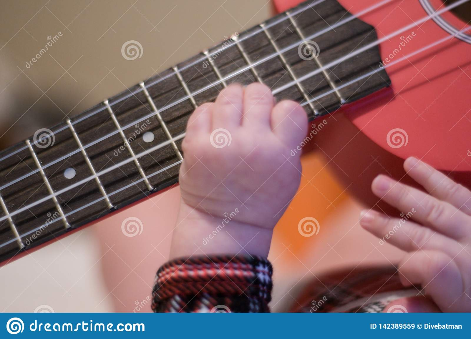 Los fingeres del bebé tocan la guitarra Secuencias y trastes del ukelele