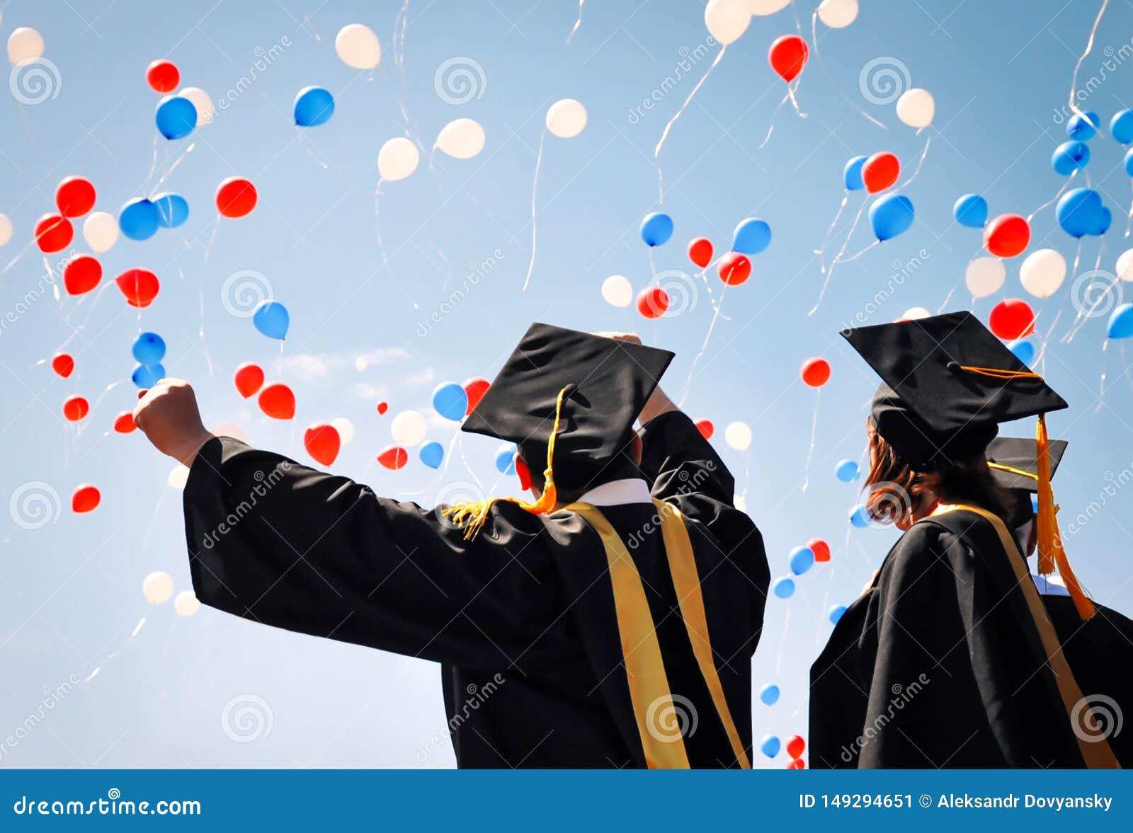 Los graduados de la universidad en trajes negros disfrutan, aumentan sus manos para arriba contra el cielo y los globos