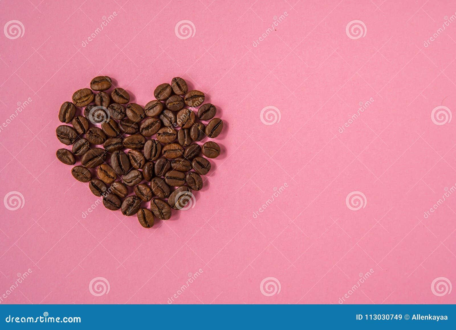 Los granos de café formaron corazones en un fondo rosado Estafa del café del amor