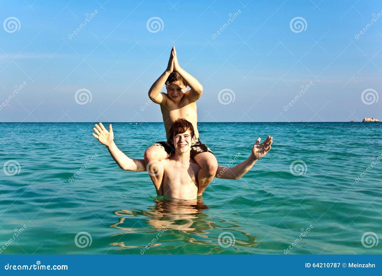 Los hermanos están gozando del agua caliente clara en el beac hermoso