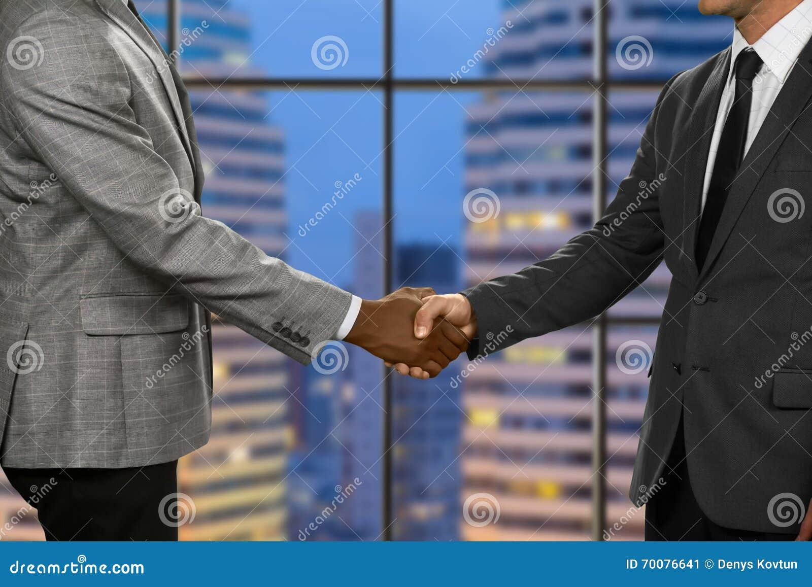Los hombres de negocios adultos sacuden las manos