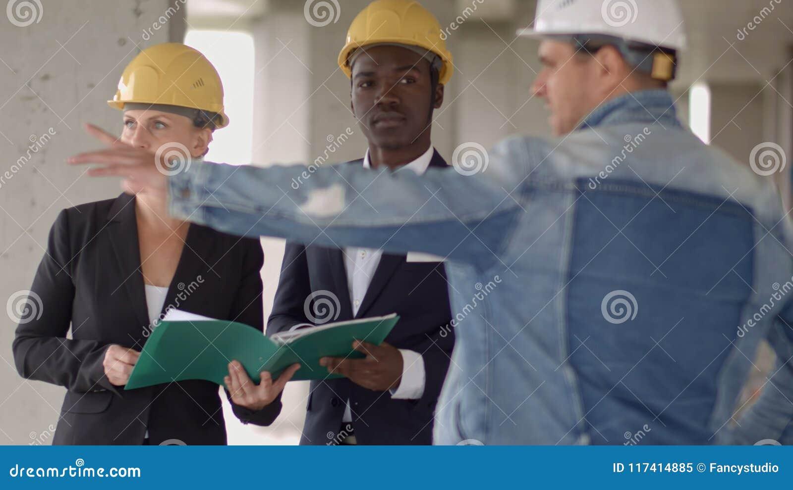 Los hombres de negocios agrupan en la reunión y la presentación en emplazamiento de la obra con el arquitecto y el trabajador del