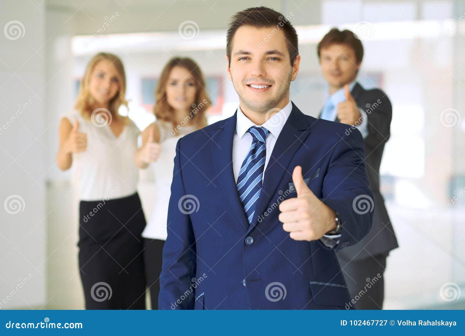Los hombres de negocios jovenes acertados que muestran los pulgares suben la muestra