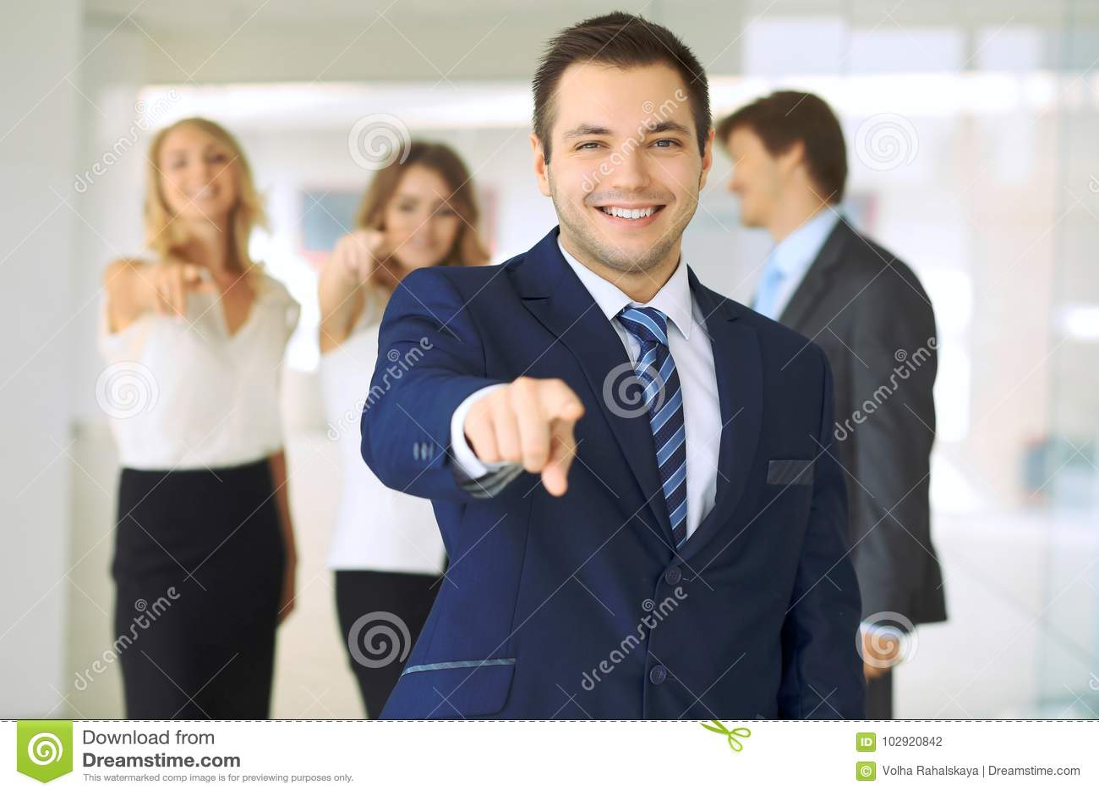 Los hombres de negocios jovenes acertados que muestran los pulgares suben la muestra mientras que se colocan en la oficina más in