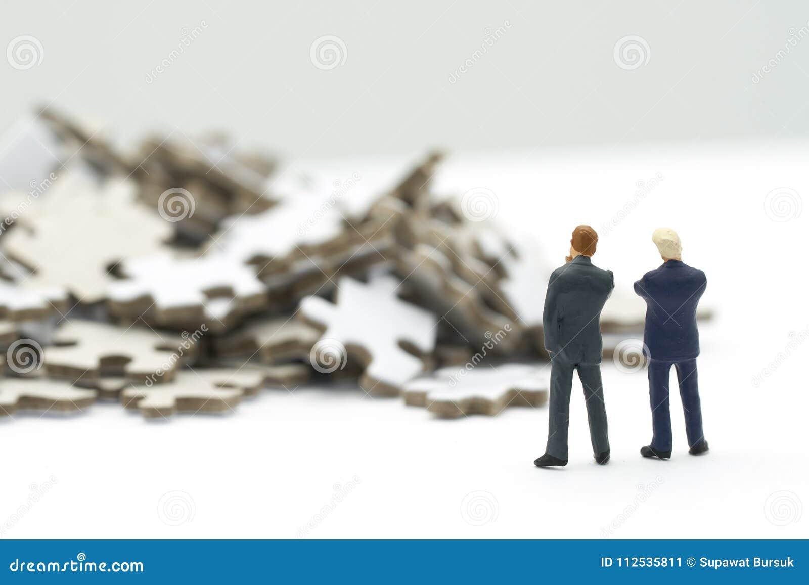 Los hombres de negocios miniatura de la gente que colocan análisis de inversión o la inversión adentro solucionan rompecabezas pa