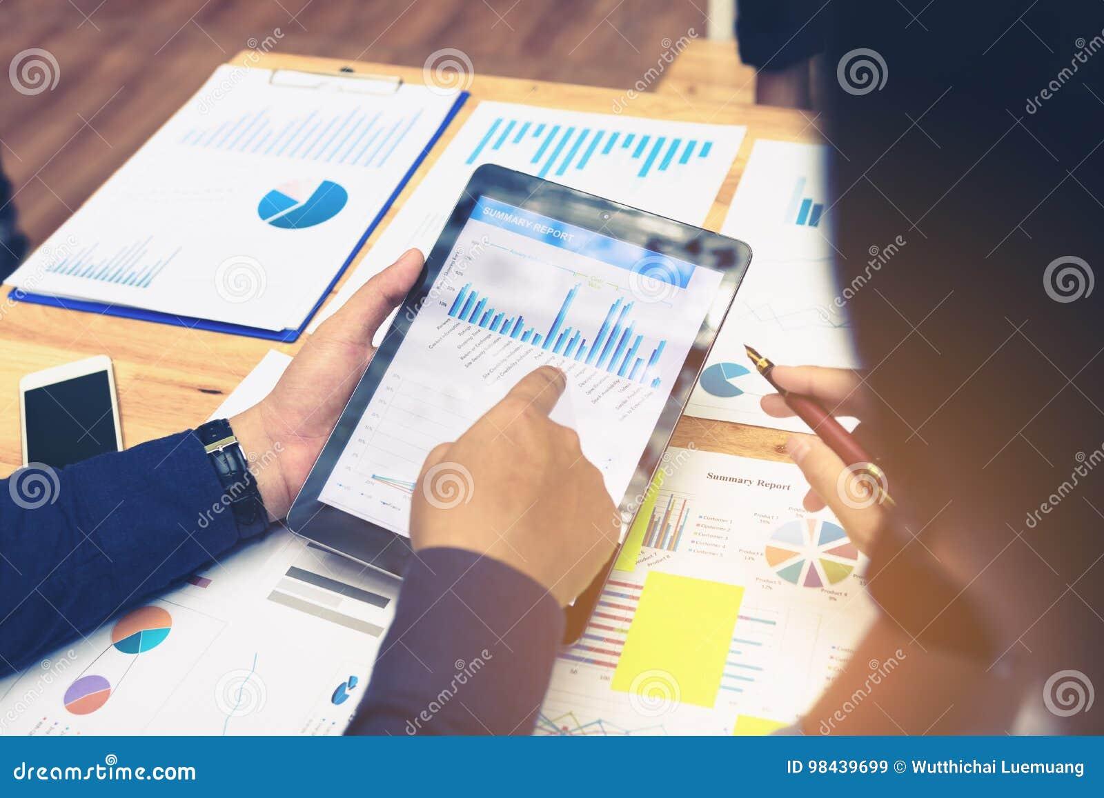 Los hombres de negocios que señalan a la pantalla de la tableta a la mirada representan el summ gráficamente