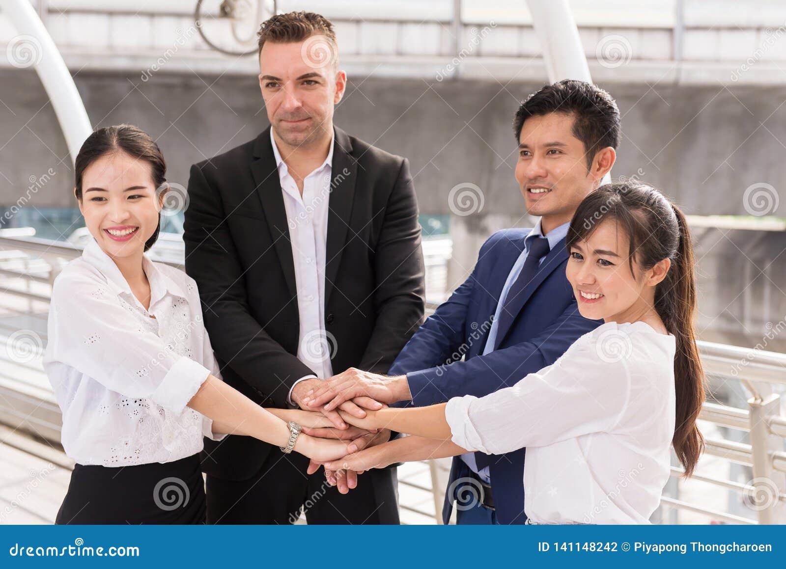 Los hombres de negocios se unen al éxito de las manos para tratar, trabajo del equipo para alcanzar las metas al aire libre, coor