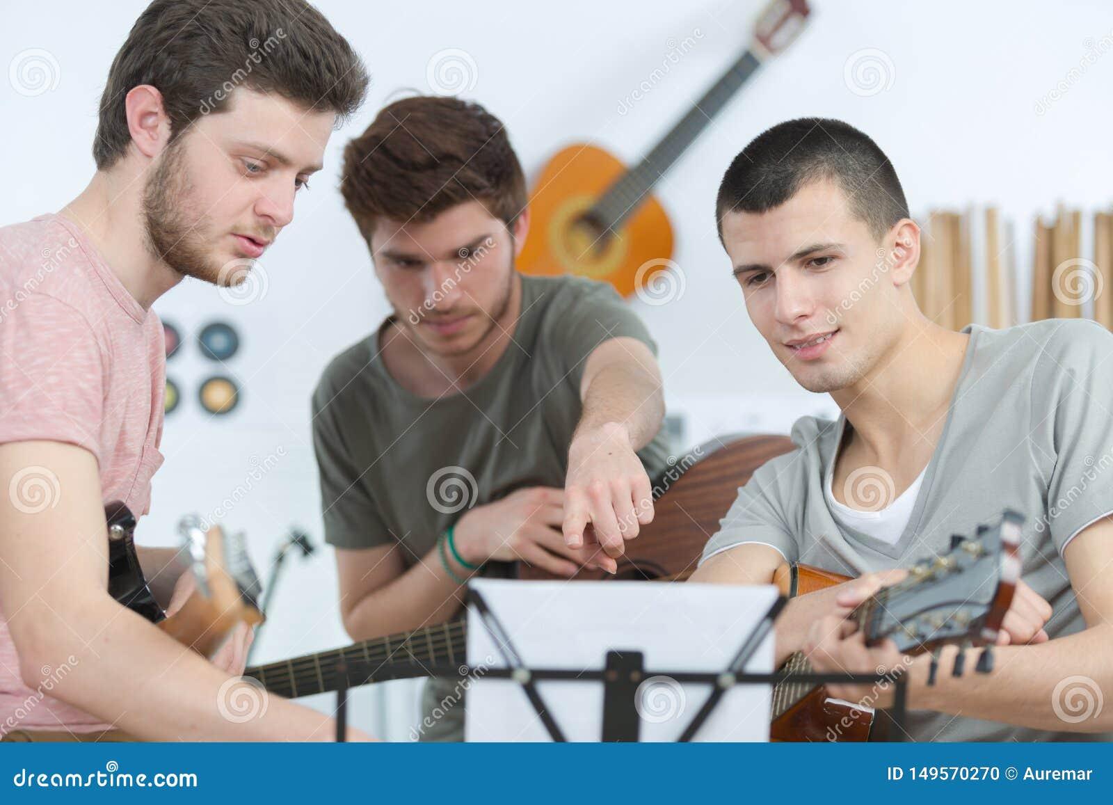 Los hombres jovenes dan tocar la guitarra en casa