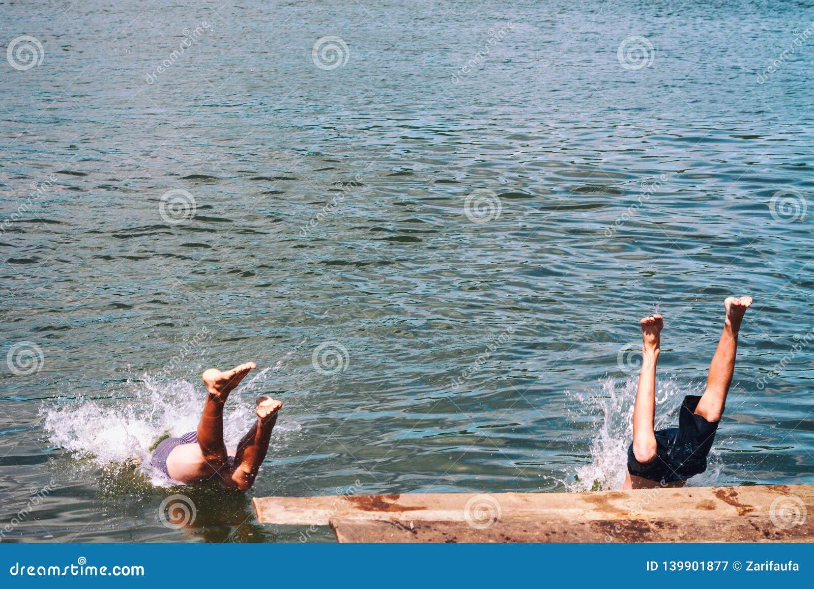 Los hombres que saltan del embarcadero de madera, pies que salpican en entrada para regar