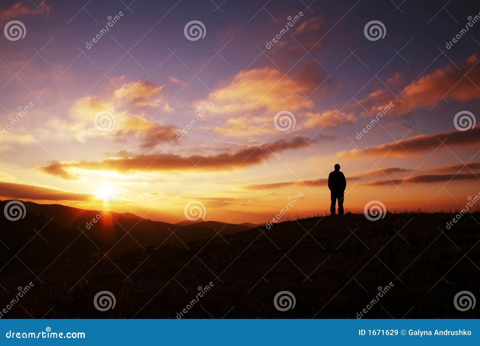 Los hombres siluetean en puesta del sol