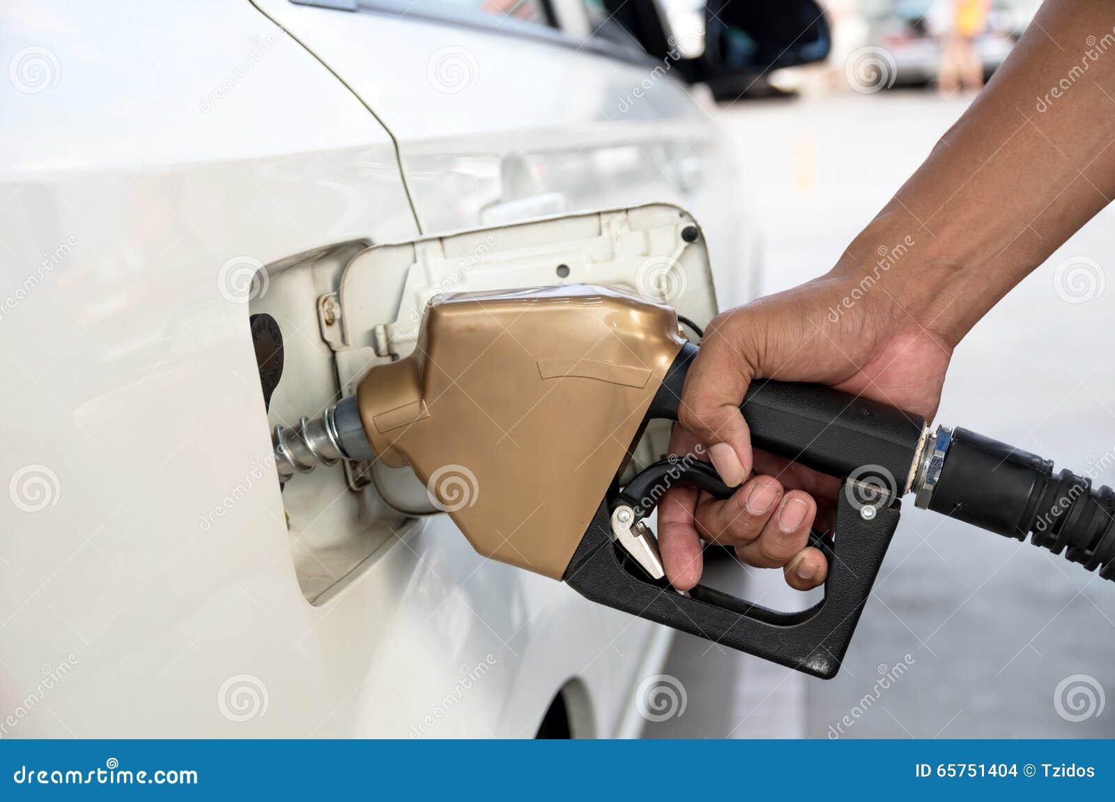 Los hombres sostienen el surtidor de gasolina para añadir el combustible en coche en la estación de servicio