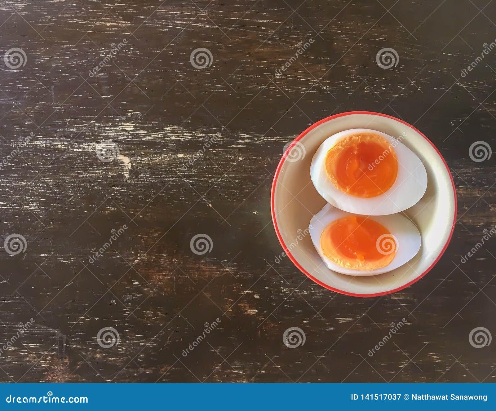 Los huevos hervidos se dividen en dos pedazos en una taza en una tabla de madera