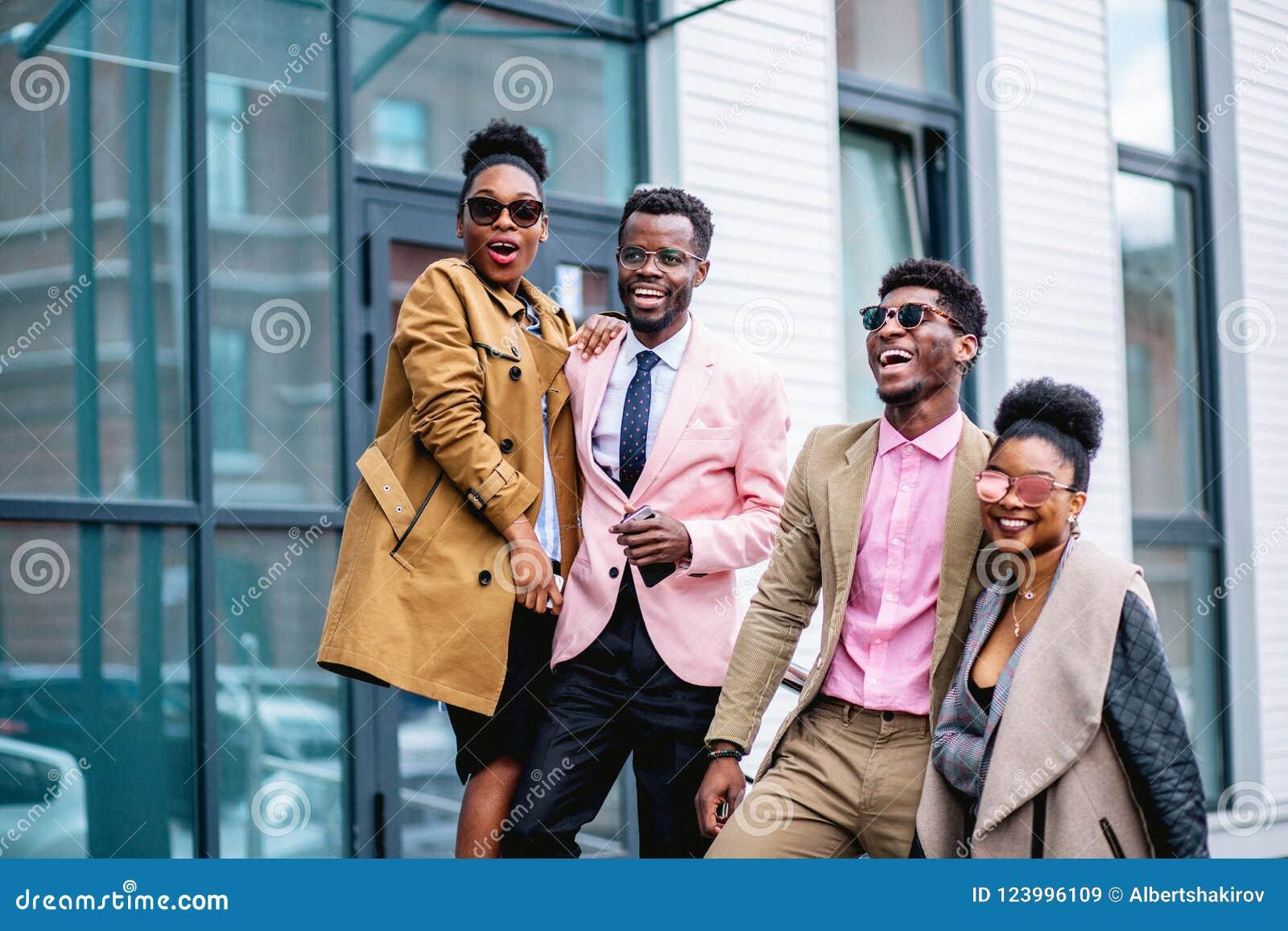 Los individuos felices con las novias se están divirtiendo en la calle