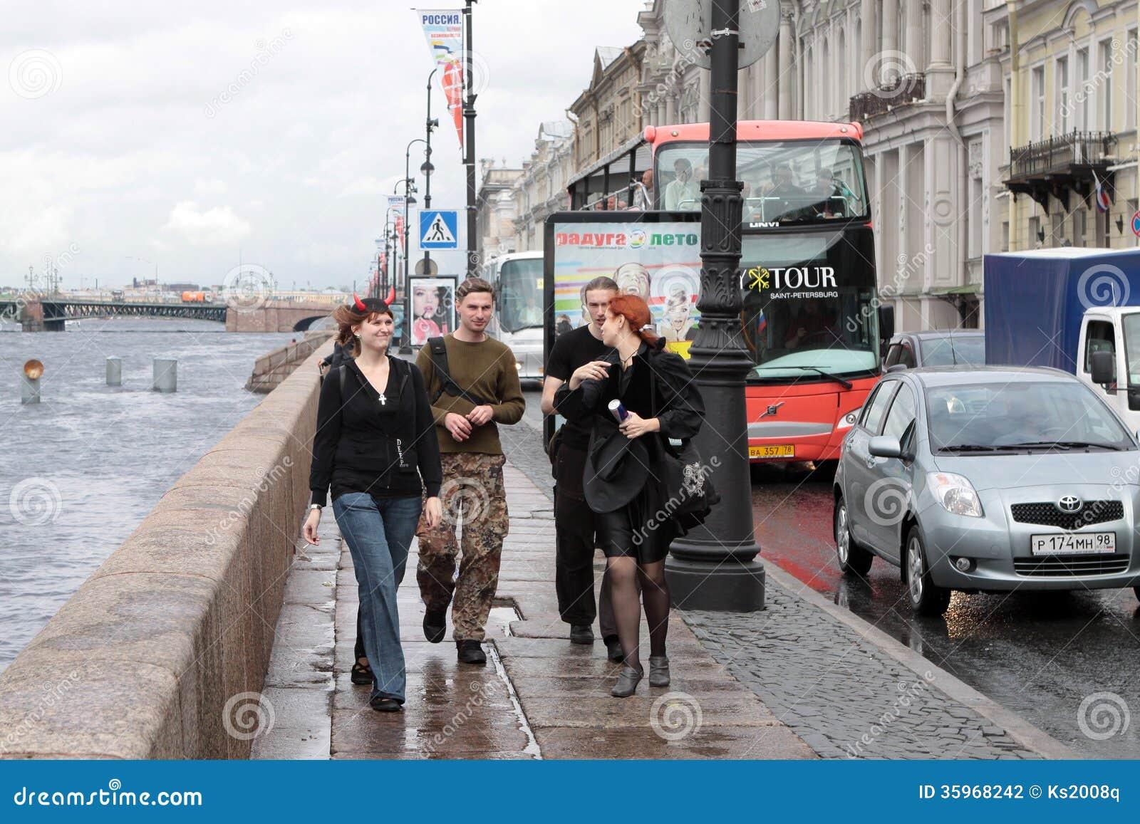 Los individuos y las muchachas jovenes en la orilla de Neva en St Petersburg