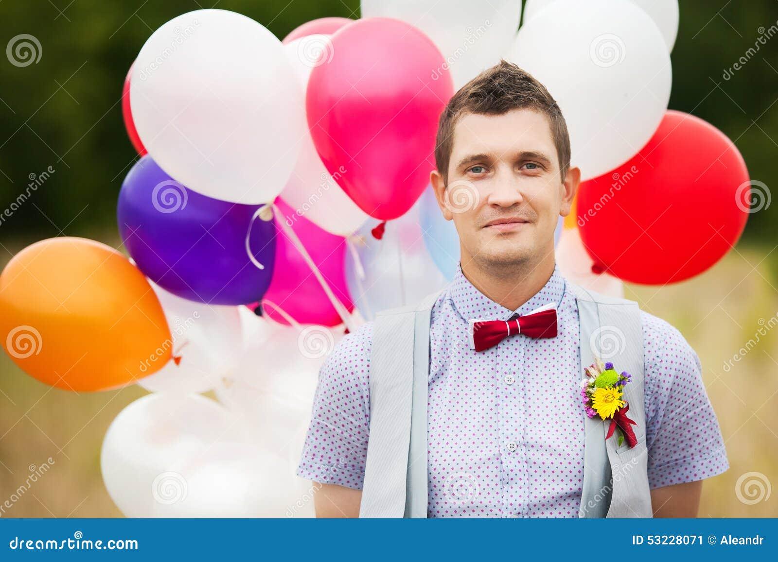 Los jóvenes felices preparan sostenerse en globos coloridos del látex de las manos