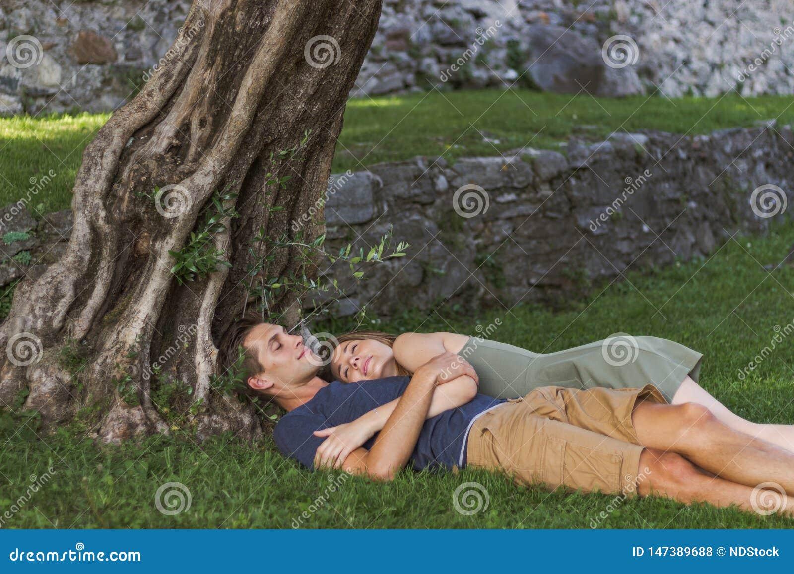 Los j?venes se juntan en el amor que se sienta debajo de un ?rbol en un castillo