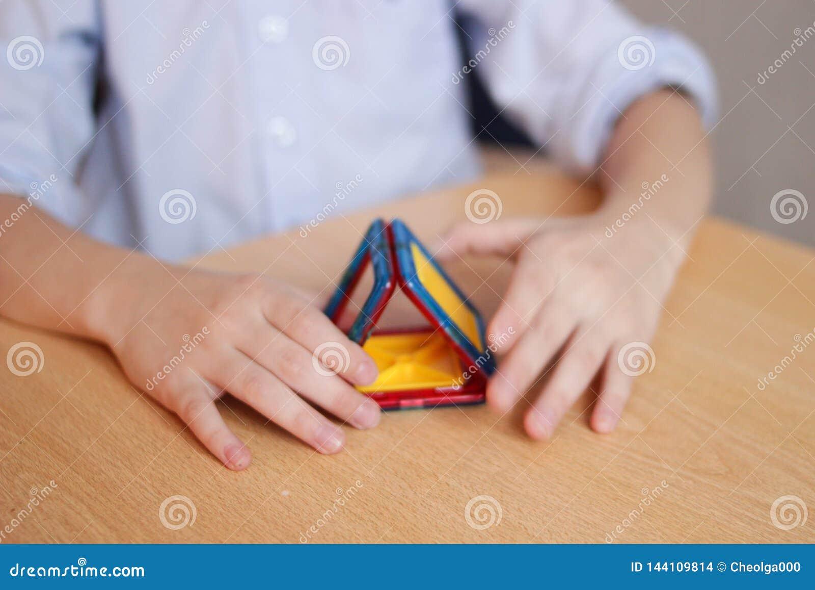 Los juegos de niños en el diseñador del color en la tabla, estructuras una casa, el concepto de una familia, el concepto de const