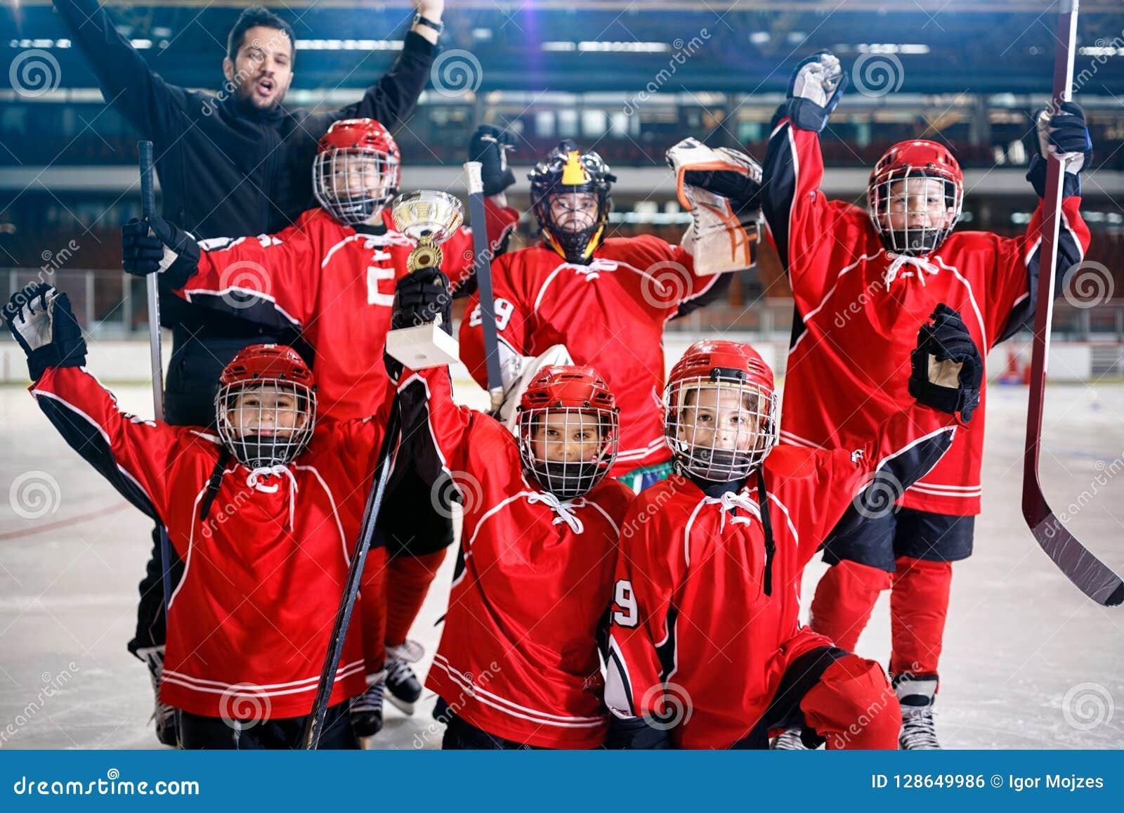 Los jugadores felices de los muchachos combinan el trofeo del ganador del hockey sobre hielo