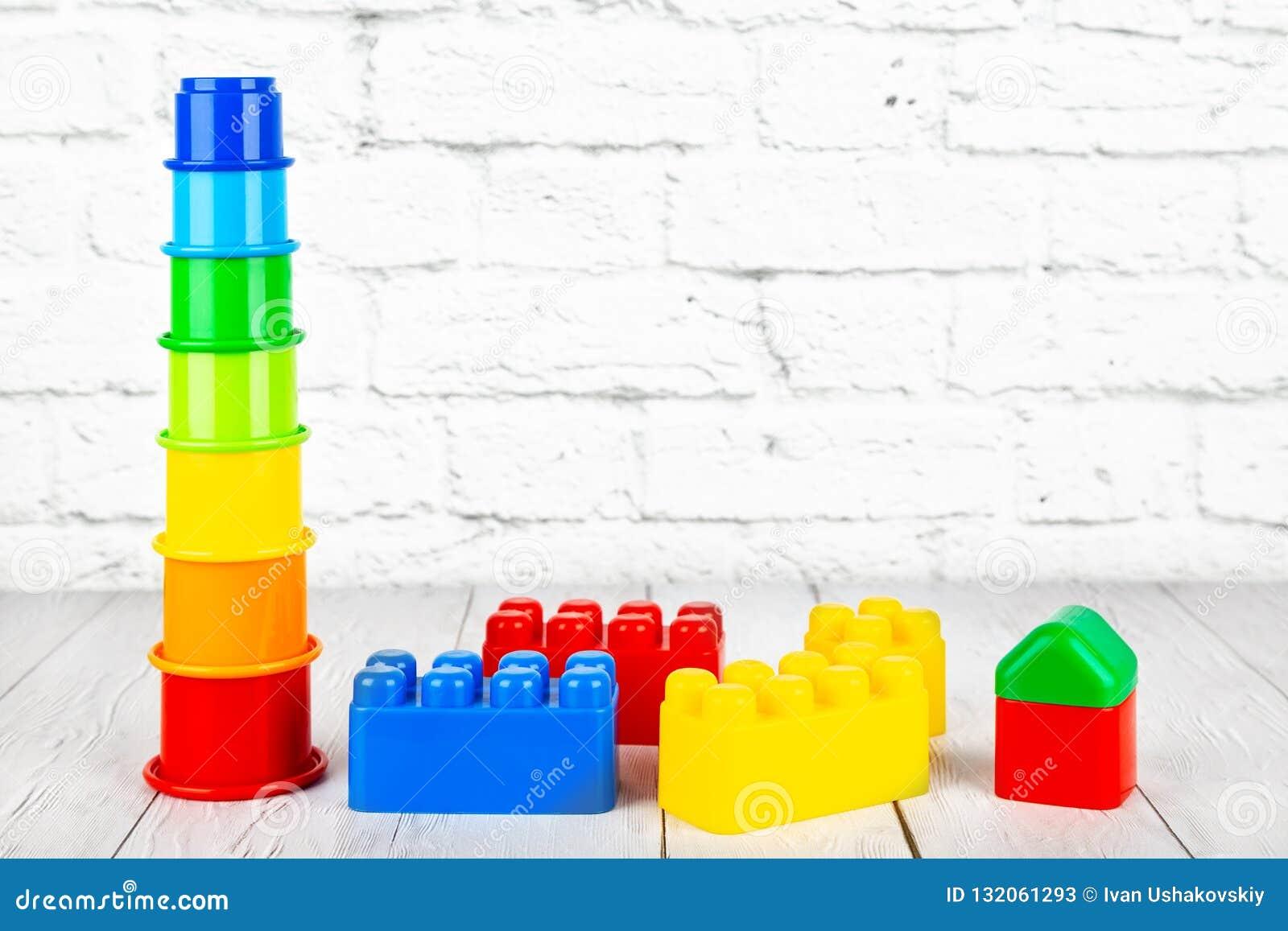 Los juguetes de los niños plásticos en la tabla de madera en un backgrou de la pared de ladrillo