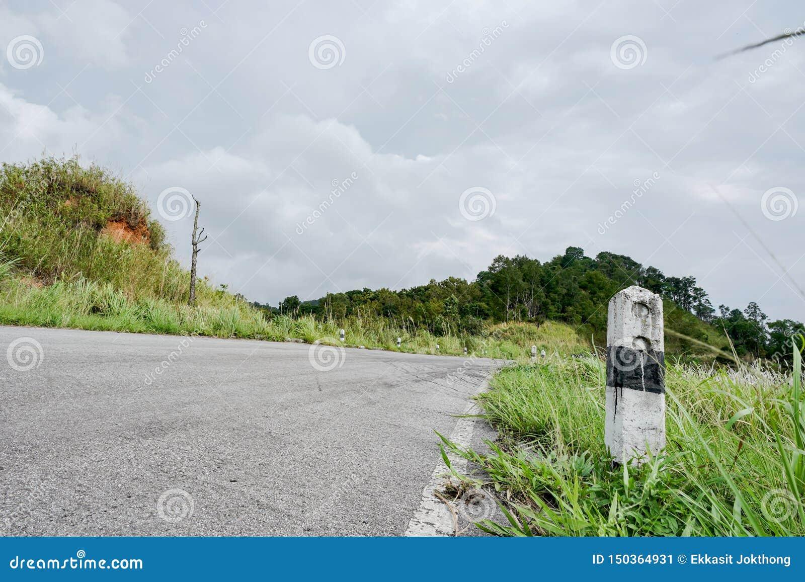 Los kilómetros blancos y negros del pilar concreto de las piedras en el camino se cubren con la hierba Con un cielo gris, kilómet
