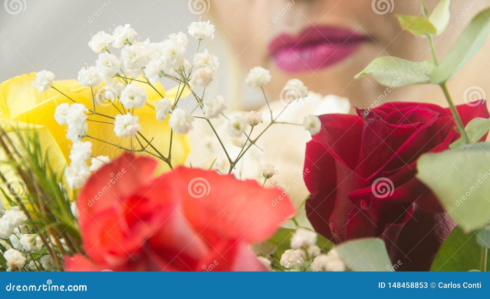 Los labios de la mujer con las flores en frente