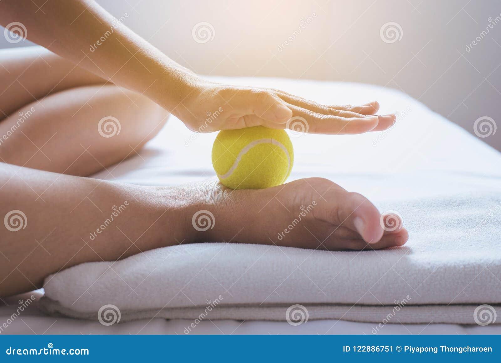 Los lenguados masaje, mano del pie de la mujer que le da masaje con la pelota de tenis se alzan en dormitorio