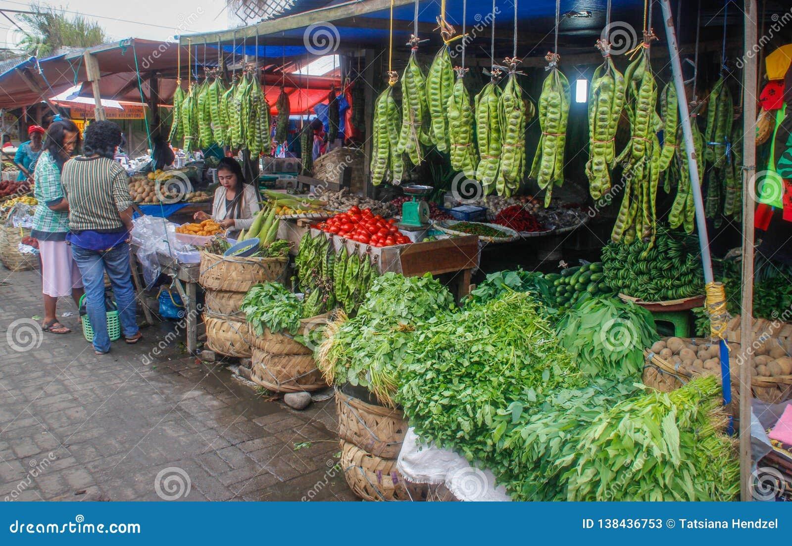 Los manojos enormes de habas verdes del gigat cuelgan en el contador en el mercado callejero indonesio