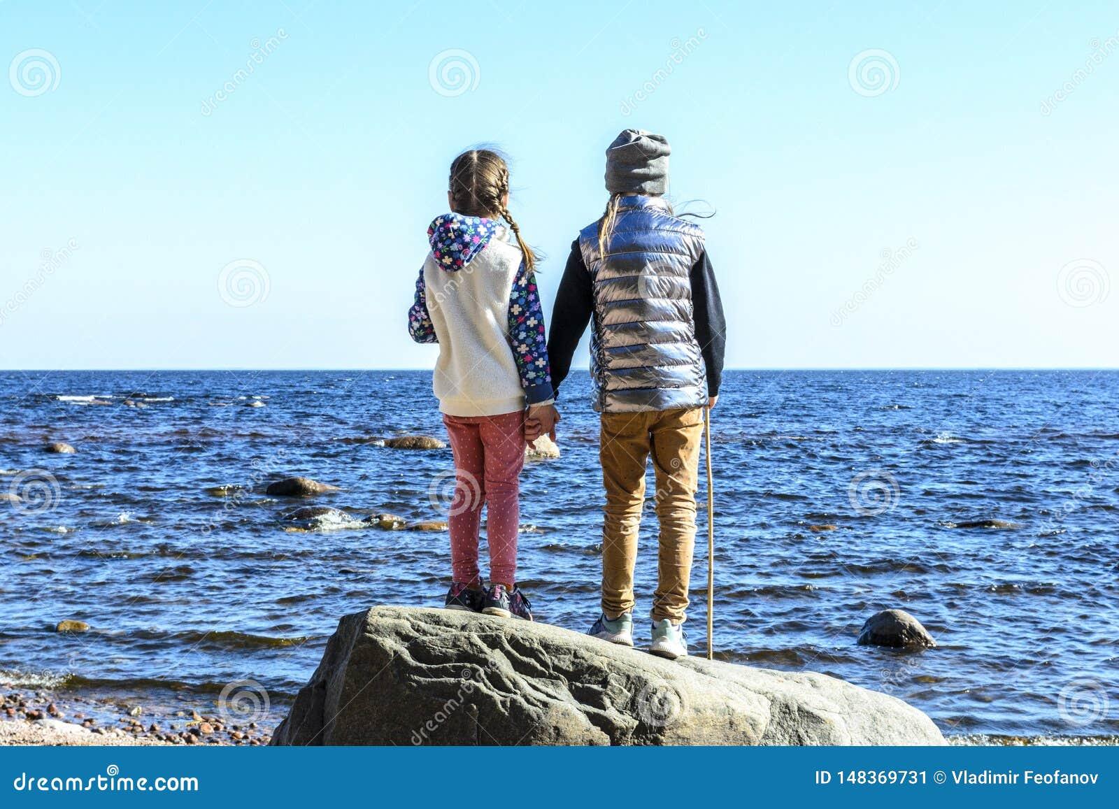 Los mejores amigos en el mundo, la proximidad y las sensaciones son limitados llevando a cabo las manos y mirando en la distancia