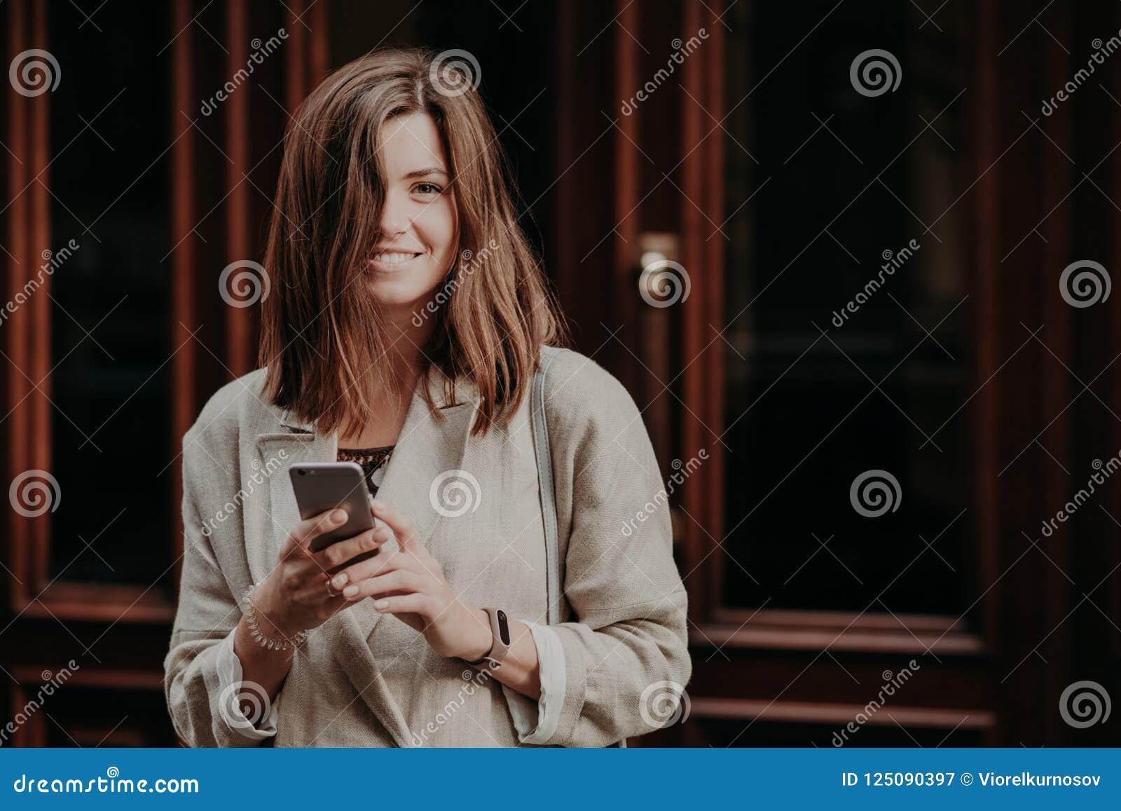 Los mensajes de textos femeninos sonrientes del blogger de los jóvenes atractivos a los seguidores, tienen tiempo de la reconstru