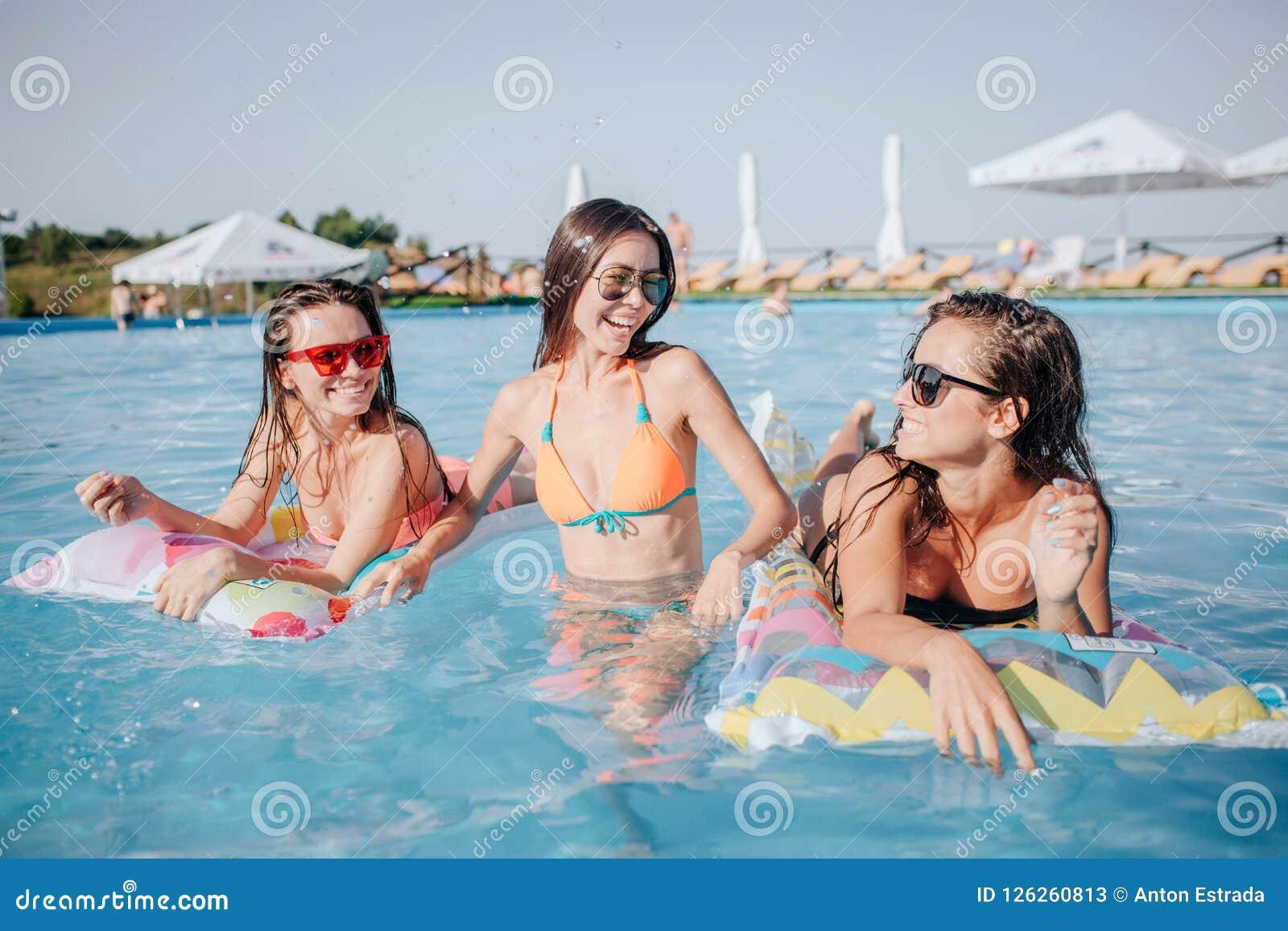 Los modelos felices están en piscina Presentan en cámara Dos modelos están mintiendo en los flotadores y miran a la mujer en cent