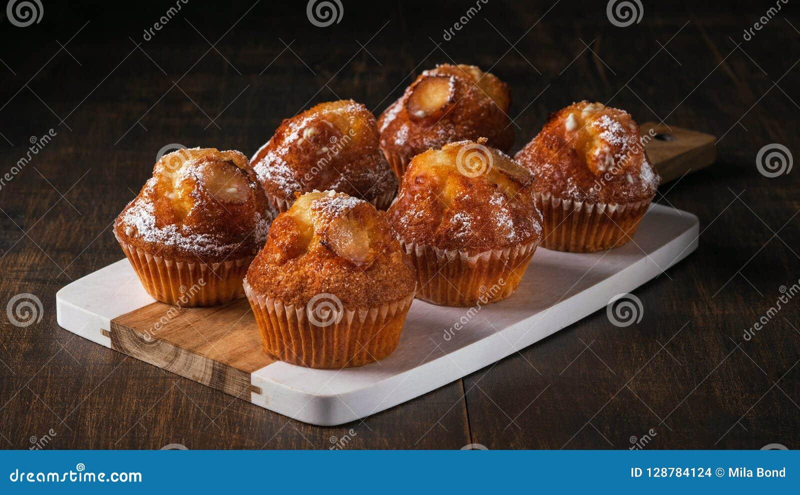 Los molletes recientemente cocidos de la vainilla con el azúcar se pulverizan, servido en el tablero de madera horizontal