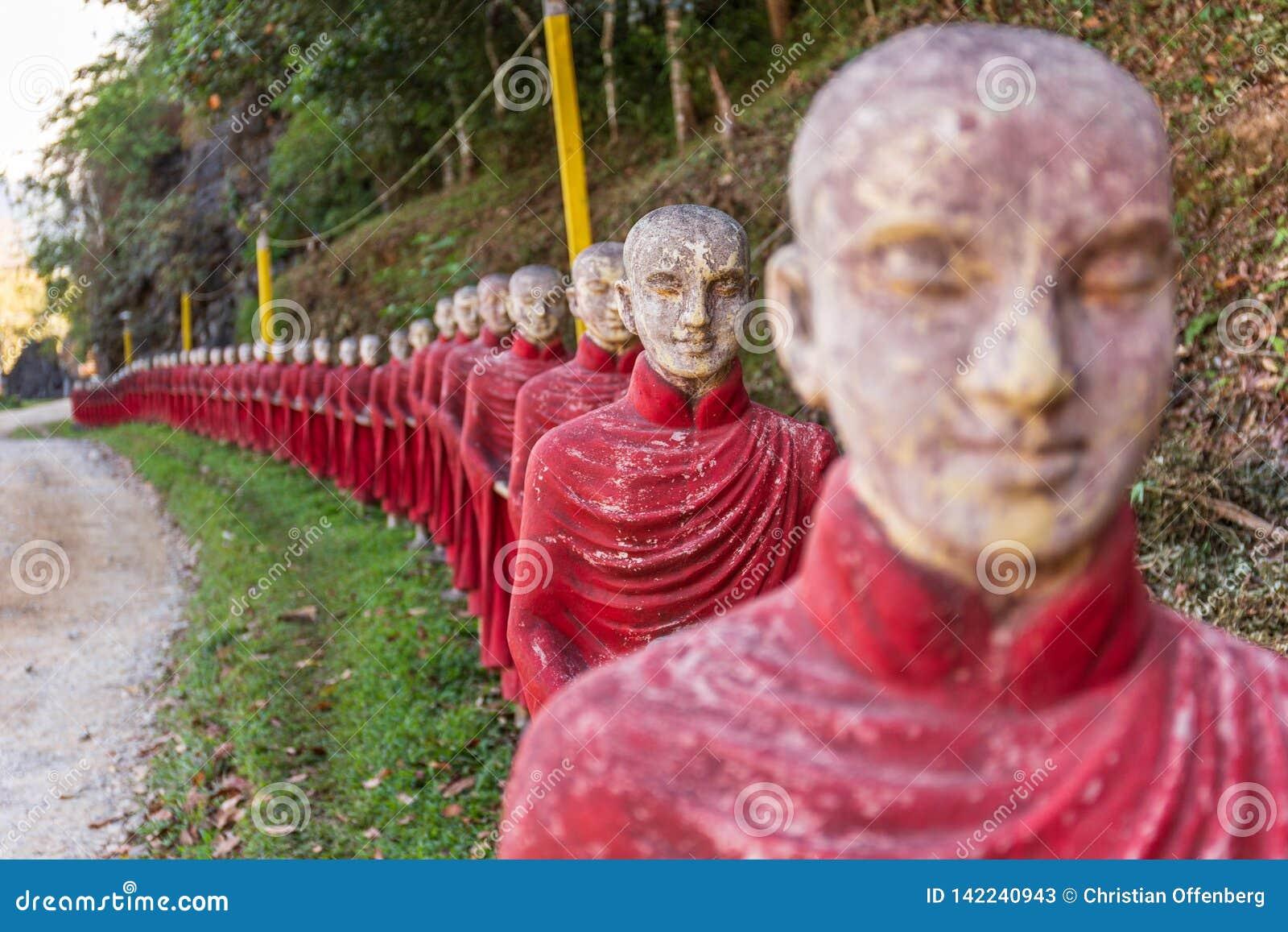 Los monjes budistas empiedran las estatuas reman en la cueva de Thaung de ka de Kaw, Hpa-an, Myanmar