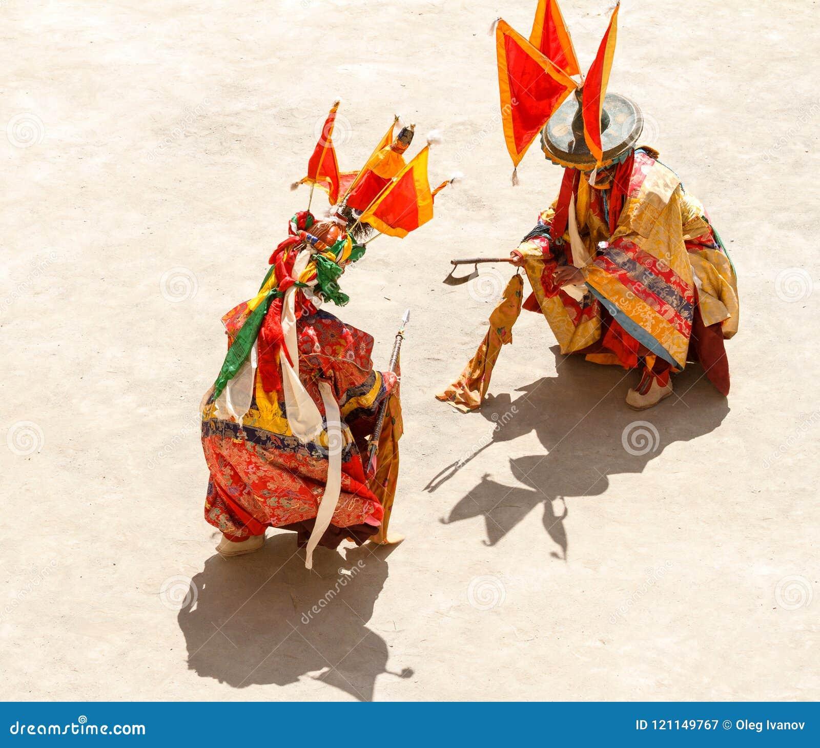 Los monjes realizan una batalla simbólica durante la danza enmascarada y vestida religiosa del misterio del budismo tibetano dura