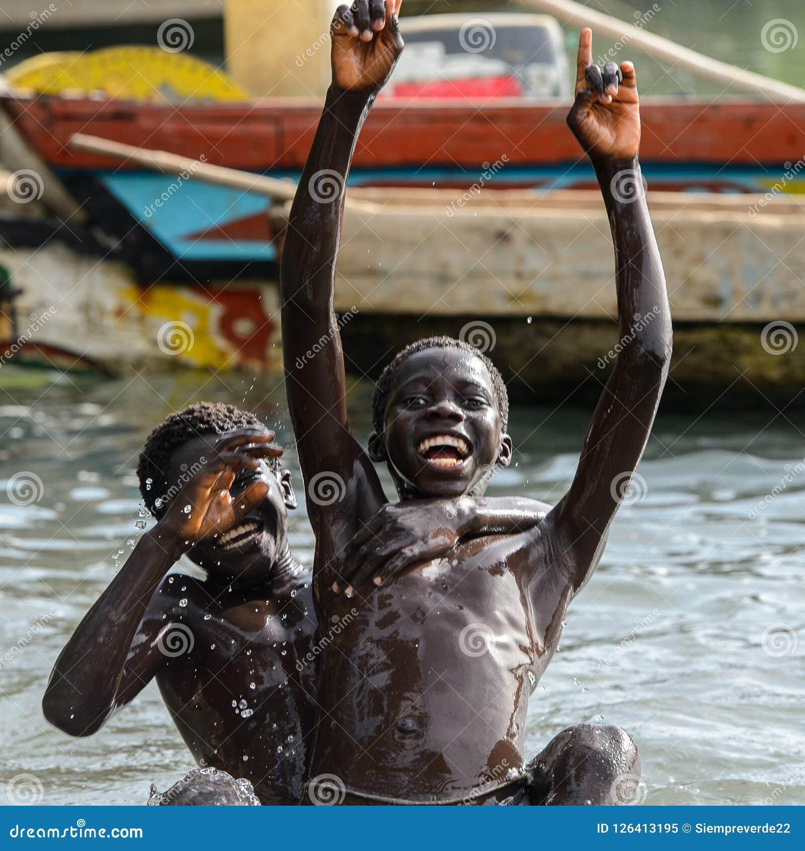 Los muchachos locales no identificados nadan en agua durante una alta marea