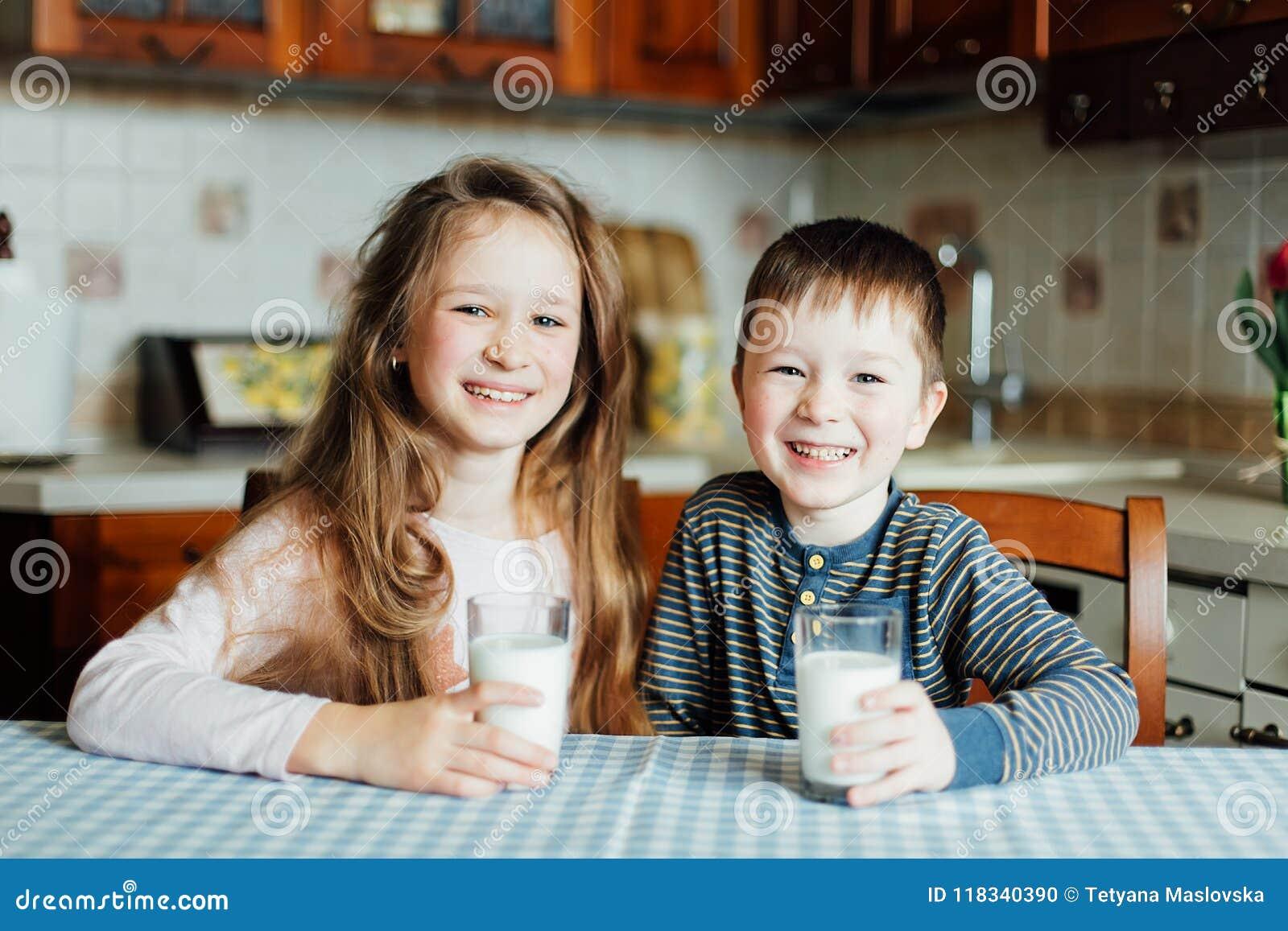 Los niños beben la leche y se divierten en la cocina en la mañana La hermana y el hermano preparan el cacao