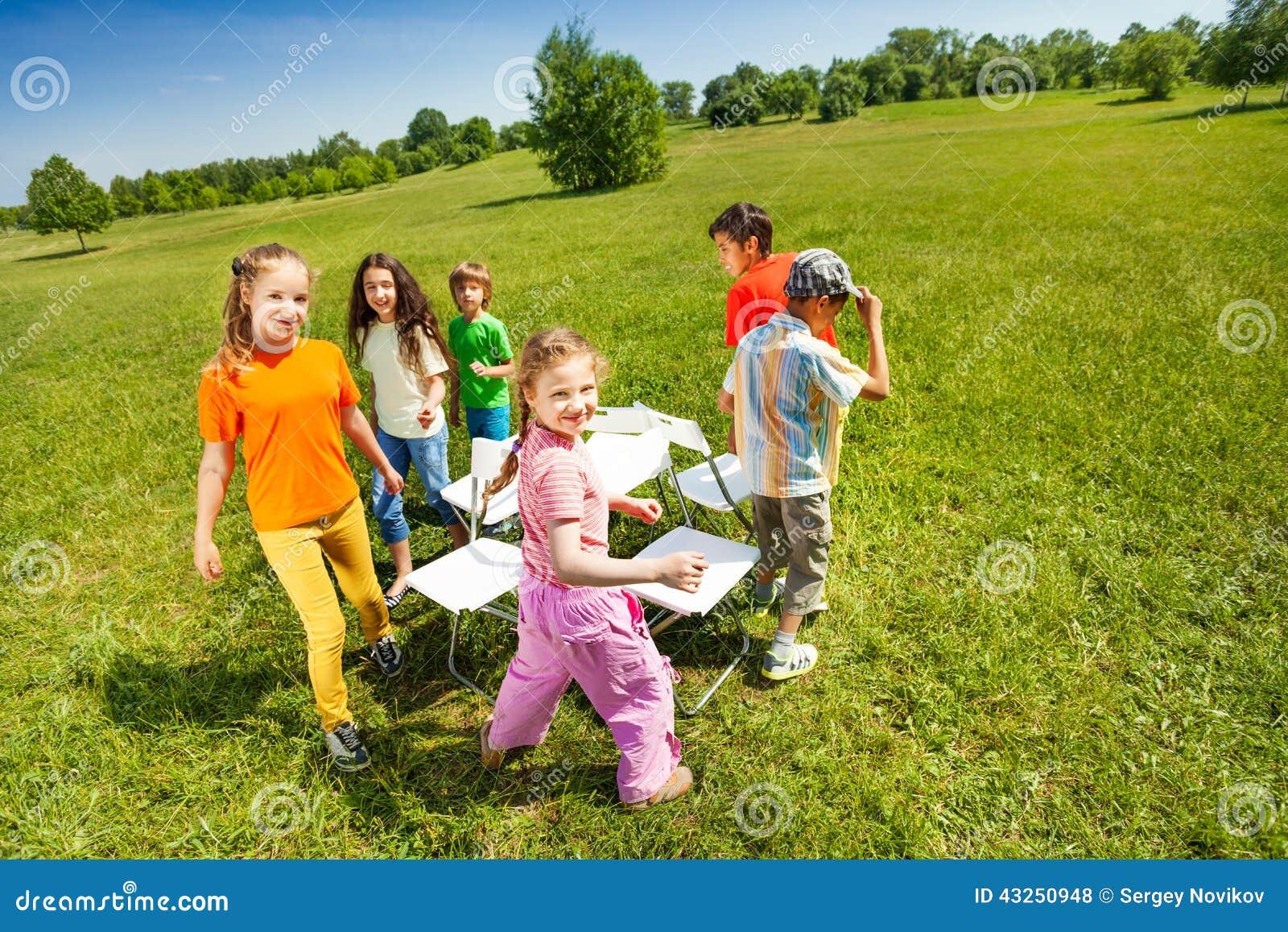 Los ni os circundan jugando sillas musicales afuera foto for Sillas para jugar ps4
