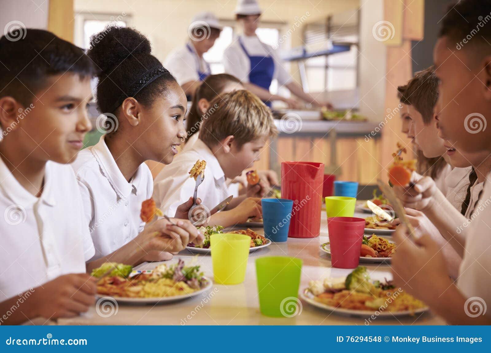 Los niños de la escuela primaria comen el almuerzo en cafetería de la escuela, cierre para arriba