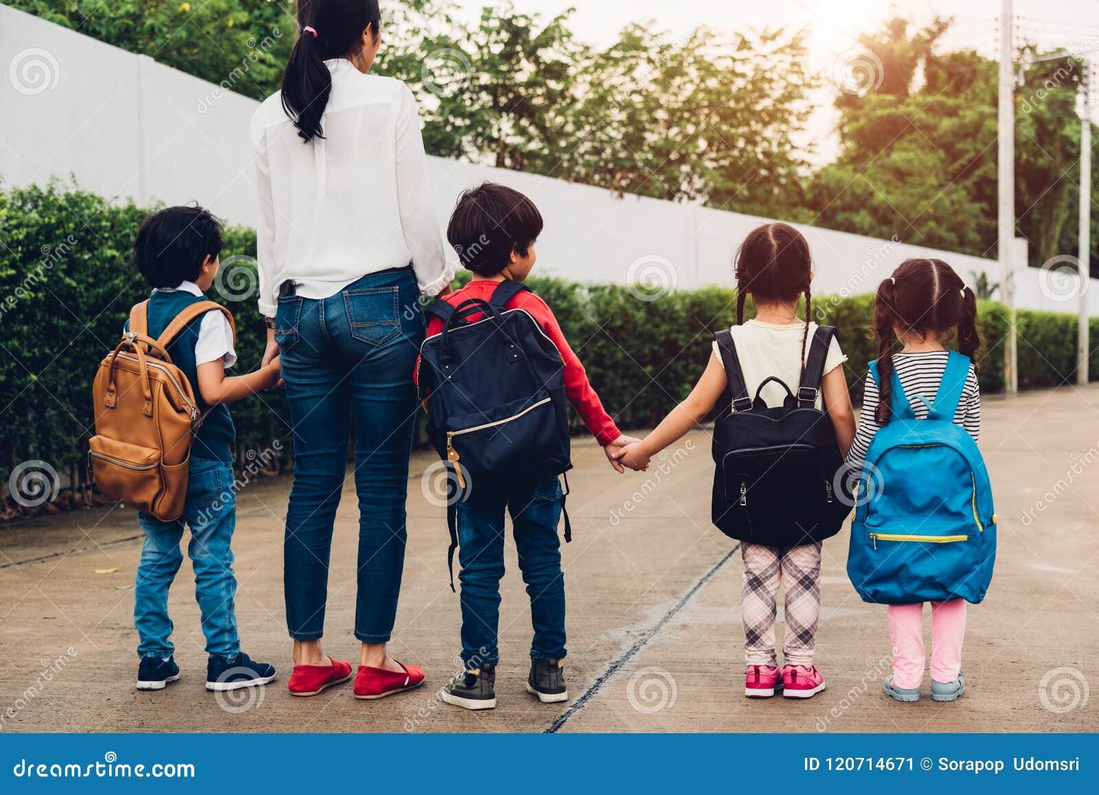 Los niños de la familia embroman ir que camina de la guardería de la muchacha y del muchacho del hijo