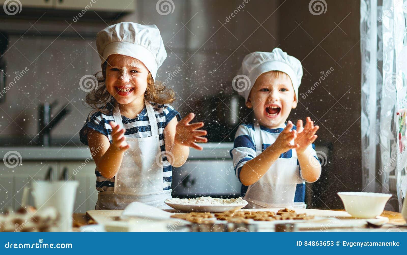 Los niños divertidos de la familia feliz cuecen las galletas en cocina