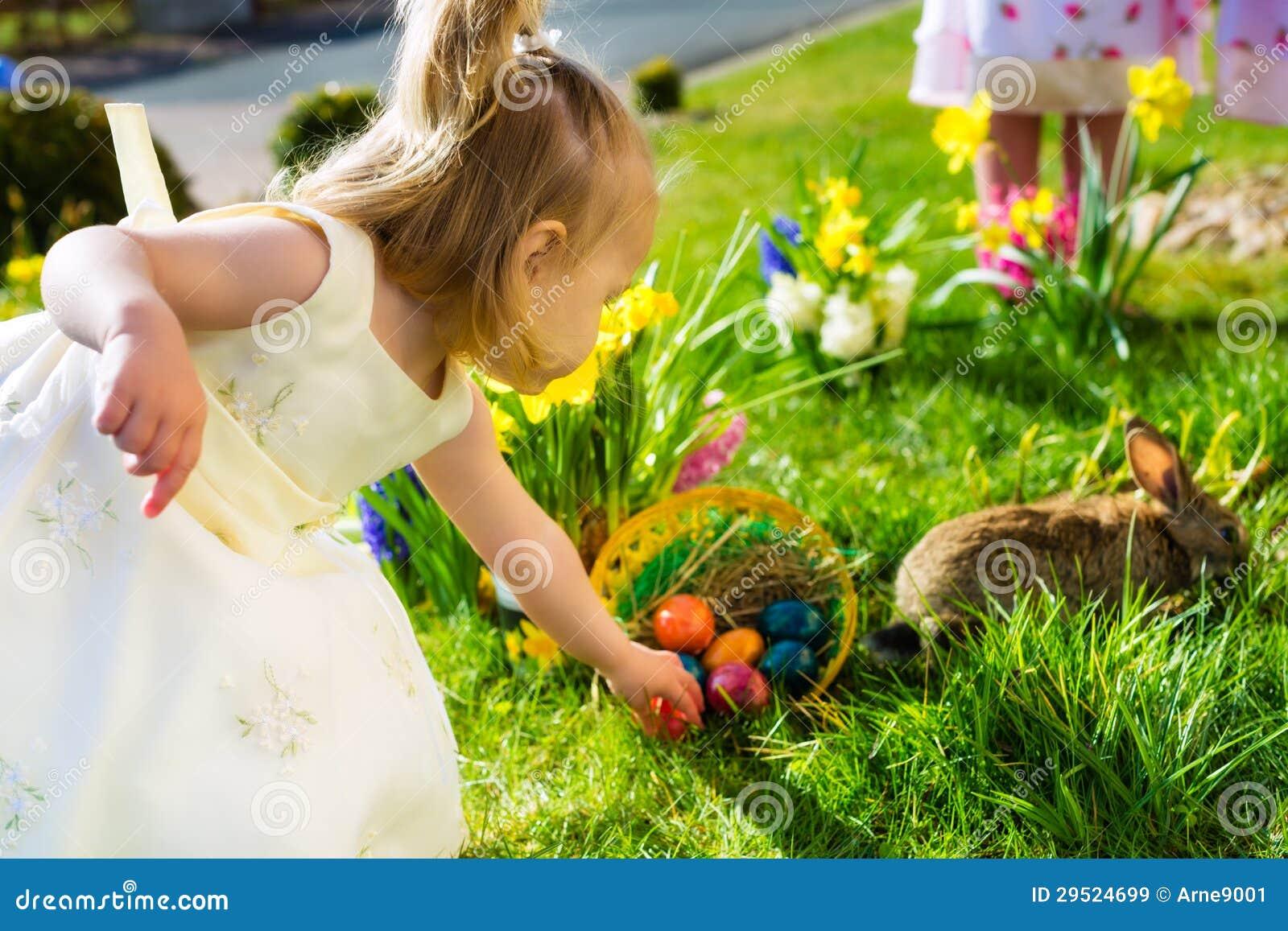 Los niños en el huevo de Pascua cazan con el conejito