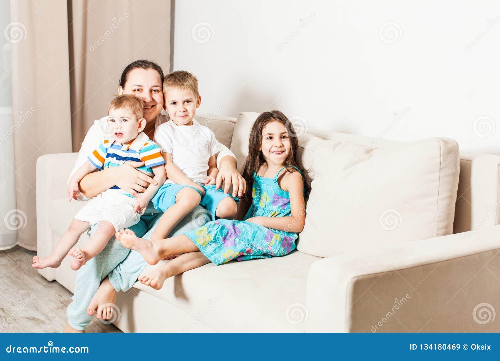 Los niños felices con la mamá se están sentando en el sofá