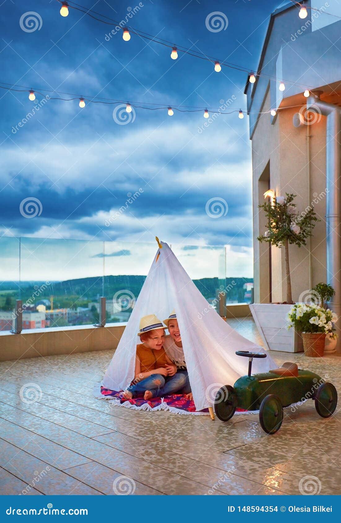 Los niños felices están ocultando en tienda india hecha a mano de una lluvia súbita del verano en el patio, jugando juntos