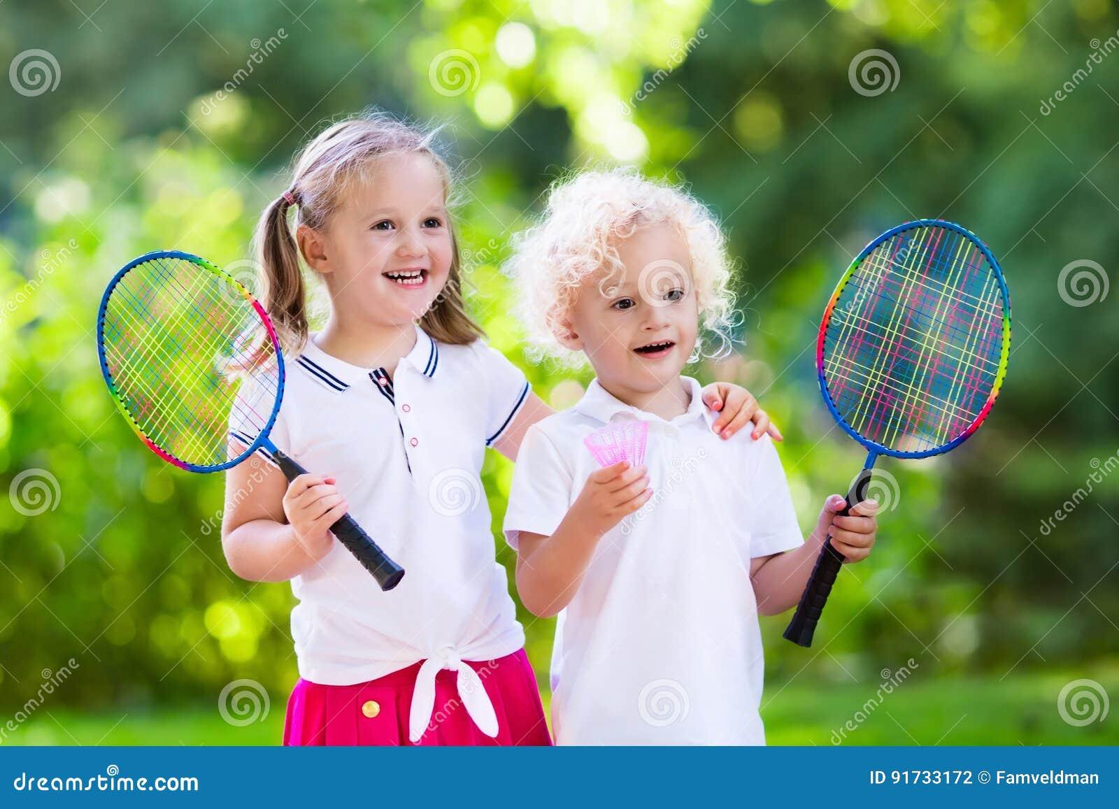 Los niños juegan a bádminton o a tenis en corte al aire libre